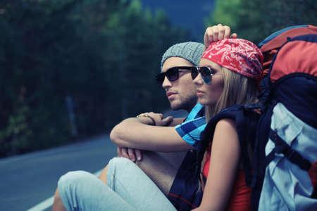 mochila viaje: Dos j�venes a turistas autostop a lo largo de una carretera.  Foto de archivo