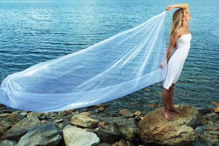 Beautiful young woman posing over sea beach. photo