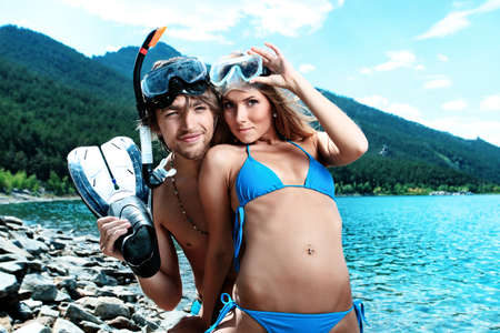 bikini couple: Happy young couple with snorkelling gear standing on a sea beach. Stock Photo