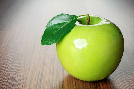 Shot of a fresh green apple with green leaf on a table. Stock Photo