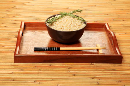 whitern: Steamed long rice in a brown bowl with chopsticks.