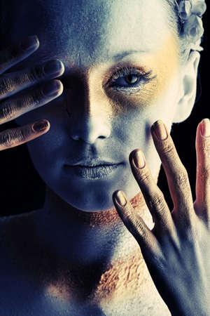 Retrato de una mujer art�stica pintado con los colores blanco y bronce, sobre fondo negro. Proyecto de pintura del cuerpo.  Foto de archivo