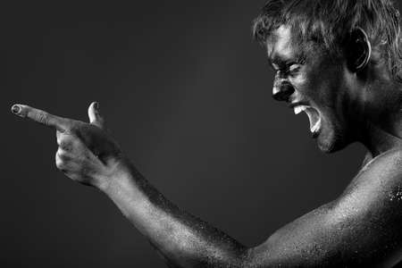 mime: Portrait of a handsome man painted with black color. Body painting project.