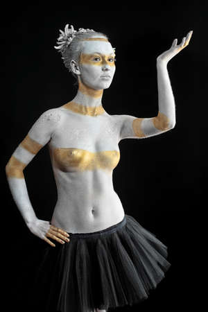 Artistic woman painted with  white and bronze colors, over black background. Body painting project. Stock Photo - 7907297