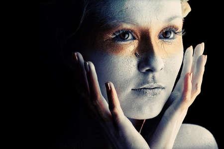 Retrato de una mujer art�stica pintado con los colores blanco y bronce, sobre fondo negro. Proyecto de pintura de cuerpo.