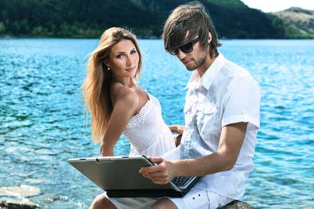 Feliz pareja joven sentados juntos cerca del mar con un ordenador port�til.