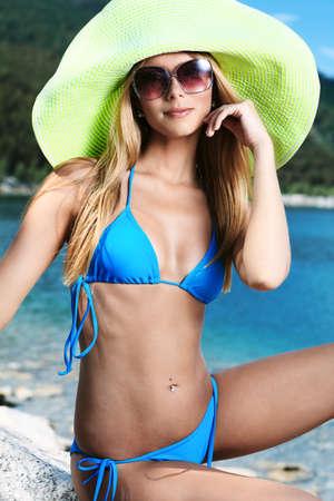 bikini slender: Beautiful young woman in bikini posing on a sea beach.