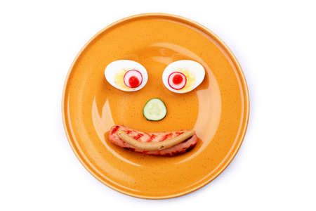 Shot of a dish with funny face made of fried sausage, egg and greens.  photo