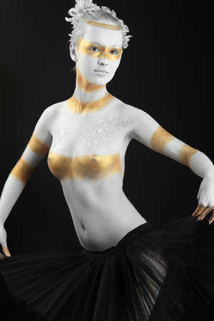 Artistic woman painted with  white and bronze colors, over black background. Body painting project.  Stock Photo - 7992416