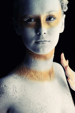 Portrait of an artistic woman painted with white and bronze colors, over black background. Body painting project.  photo