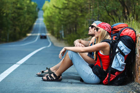 hitchhiking: Two young people tourists hitchhiking along a road.