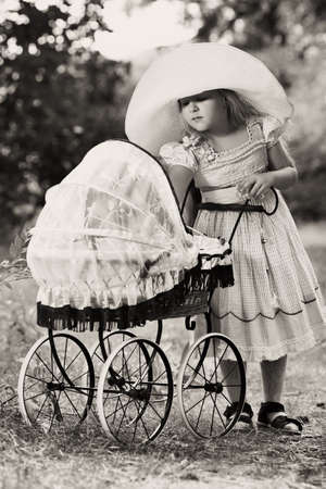 Shot of a cute girl walking with baby buggy at summer park. Stock Photo - 7992464