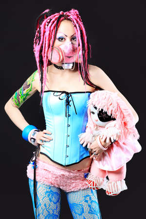 Cosplay young woman in respirator holding a doll over black background. photo