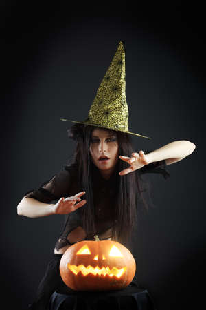 Halloween witch with a broom and carved pumpkin over black background. photo