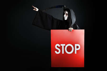 Woman death reaper over black background. Halloween. Stock Photo - 7992489