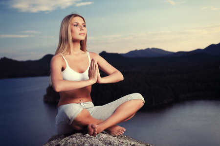 Slender young woman doing yoga exercise outdoors. Stock Photo - 7992536