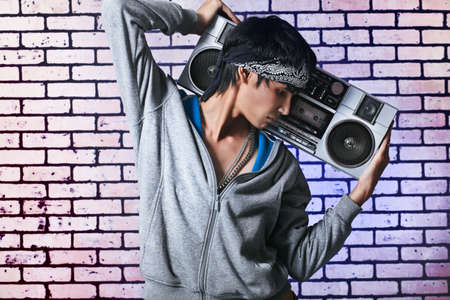 Trendy young man posing  against a brick wall with tape recorder. Stock Photo - 8062519