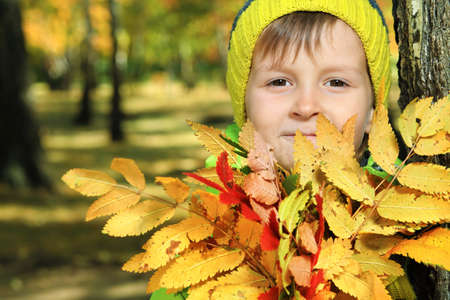 Happy little boy walking at the autumn park. photo