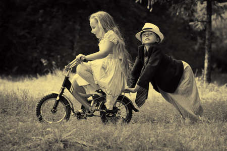 weekend activities: Cute children  is riding a bike in a summer park. Retro style.