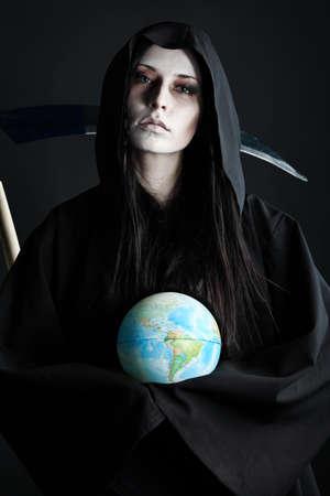 scythe: Reaper de muerte de mujer con un globo sobre fondo negro. Halloween.  Foto de archivo