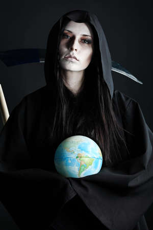scythe: Woman death reaper with a globe over black background. Halloween. Stock Photo