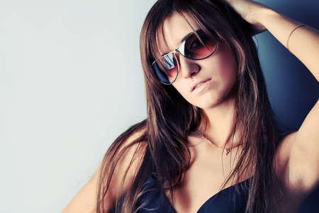 Portrait of a fashionable woman in sunglasses. Studio shot. Stock Photo - 8077005