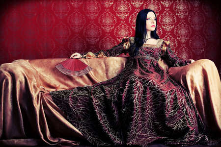 Portrait of a beautiful woman in medieval era dress. Shot in a studio. photo