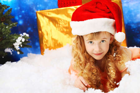 Christmas kid in Santa hat sitting in snowdrift. Stock Photo - 8108096
