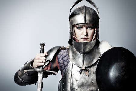 medieval woman: Portrait of a medieval female knight in armour over grey background.