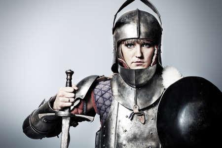 espadas medievales: Retrato de un caballero medieval femenino en armadura sobre fondo gris.