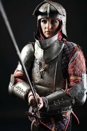 ancient warrior: Portrait of a medieval female knight in armour over black background.
