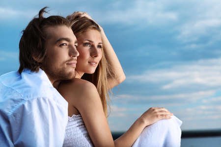 Beautiful young couple posing together over blue sky. Stock Photo - 8159985