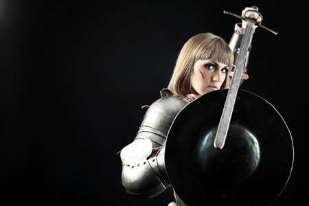 traditional weapon: Portrait of a medieval female knight in armour over black background.