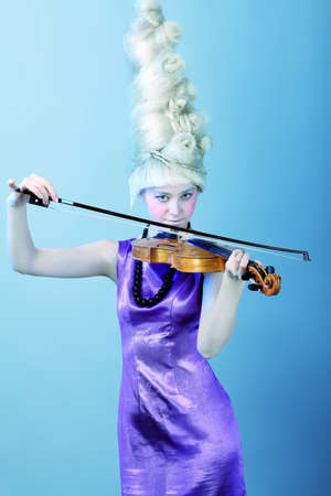 rosin: Portrait of an artistic young woman posing with violin. Isolated over white background. Stock Photo