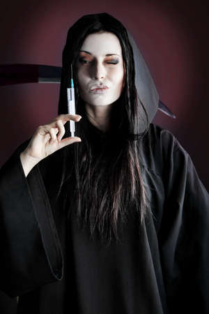 Woman death reaper with syringe over black background. Stock Photo - 8160394