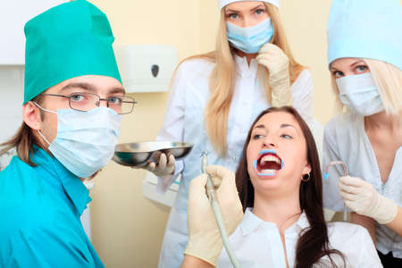 Shot of a young woman with dentists in a dental surgery. Healthcare, medicine.