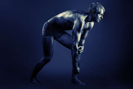 Portrait of a muscular man painted with black color. Body painting project. photo