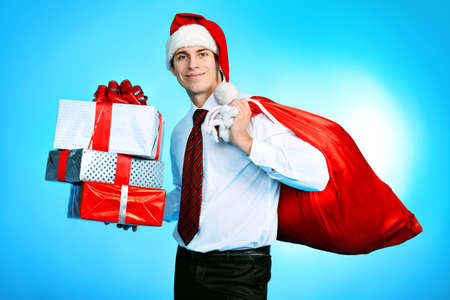Portrait of a handsome business man in Santa Claus hat holding presents. Christmas. photo