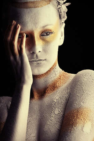 bodypainting: Portrait of an artistic woman painted with white and bronze colors, over black background. Body painting project.  Stock Photo