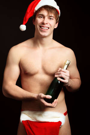 Portrait of a handsome muscular young man in Santa Claus hat celebrating Christmas. photo