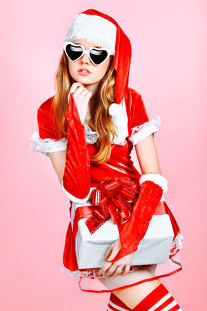 Beautiful young woman in Santa Claus clothes over pink background. photo