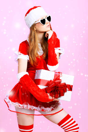 Beautiful young woman in Santa Claus clothes over pink background. Stock Photo - 8217465