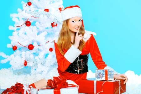 Beautiful young woman in Santa Claus clothes over Christmas background. Stock Photo - 8217458