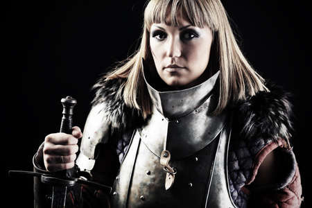 medieval woman: Portrait of a medieval female knight in armour over black background.