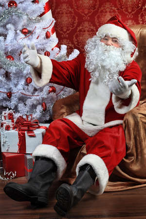 Santa Claus with presents and New Year tree at home. Christmas. Stock Photo - 8217537