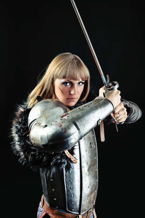 female fighter: Portrait of a medieval female knight in armour over black background.