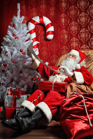 Santa Claus with presents and New Year tree at home. Christmas. Stock Photo - 8217541