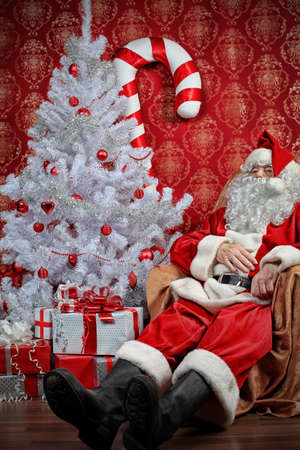 Santa Claus with presents and New Year tree at home. Christmas. Stock Photo - 8217546