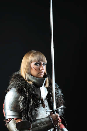Portrait of a medieval female knight in armour over black background. Stock Photo - 8217526