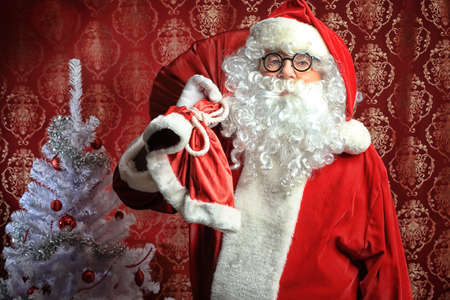 saint nick: Santa Claus with presents and New Year tree at home. Christmas.